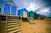 stock photo of beach hut  - Colourful beach huts with dramatic sky - JPG