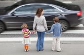 image of zebra crossing  - young mother holds hand of his little daughter and son and standing near cross road - JPG