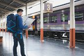 Asian Man With Backpack Standing On Platform At Train Station. Backpacker Or Traveler Look At Map Wh poster