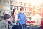 Teacher and mother with sons on meeting at school library poster