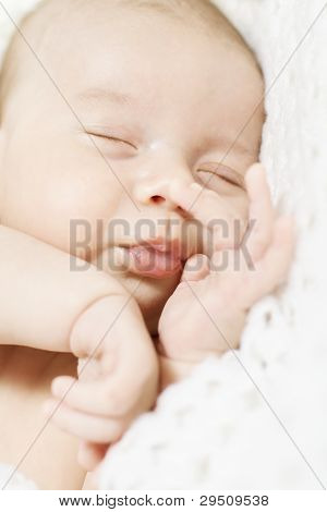 Closeup Of Sleeping Newborn Baby  Over White Blanket