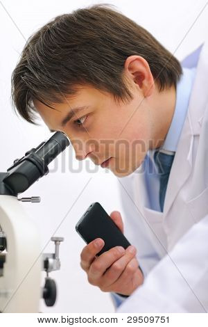 Researcher Looking In Microscope And Making Notes On Voice Recor