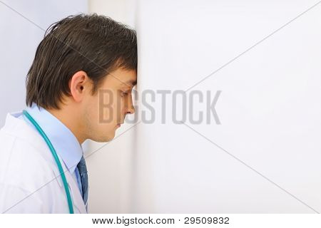 Tired Medical Doctor Leaned His Head Into A Wall