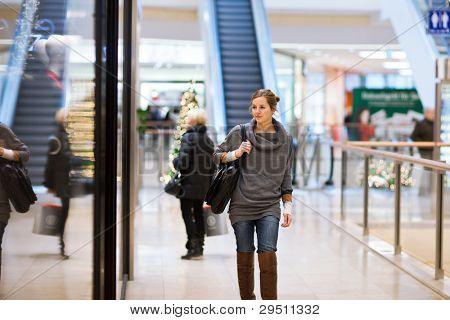 Jovem mulher olhando a loja do windows ao fazer compras em um shopping center/centro