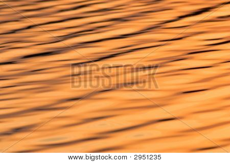 Water Texture With Small Waves And Reflection Of Orange Sky