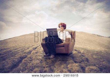 Young man sitting on an armchair on a field and using a laptop