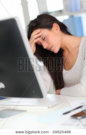 Woman in front of desktop computer having a headache