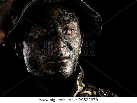 portrait of a young soldiers face with jungle camouflage over a black background