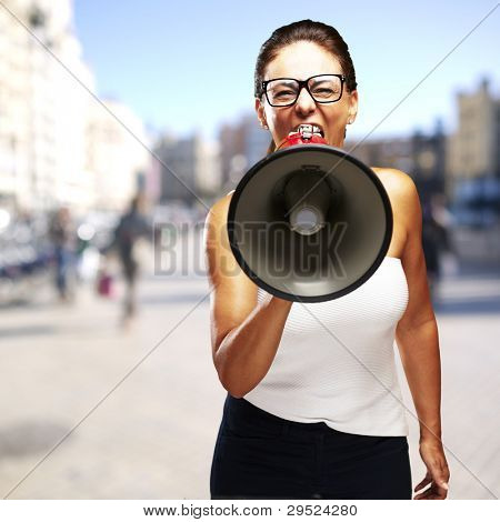 portrait of a middle aged woman shouting with a megaphone at a crowded place