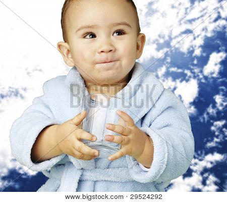 portrait of an adorable infant with a blue bathrobe holding a glass against a cloudy background
