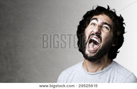 portrait of a young man shouting against a grey wall