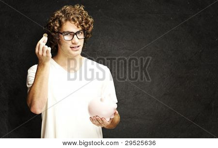 portrait of a young man holding a coin and a piggy bank against a grunge wall