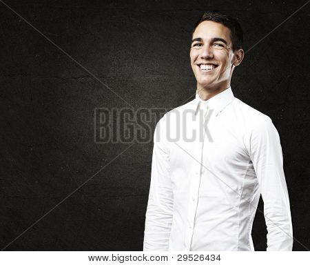 portrait of a young man with a shirt smiling against a grunge wall