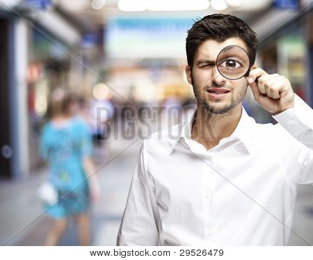 portrait of a young man holding a magnifying glass against a street background
