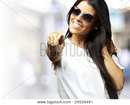 portrait of a young woman wearing heart sunglasses pointing at a crowded place
