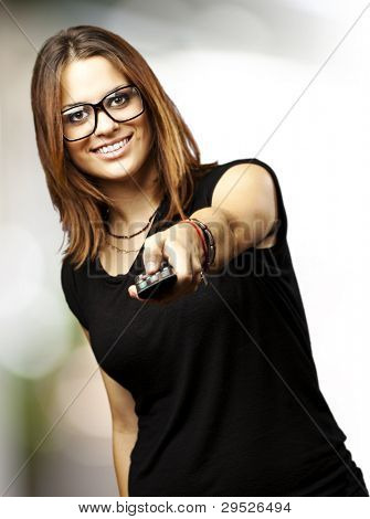 portrait of a young woman with glasses changing channel with a remote control