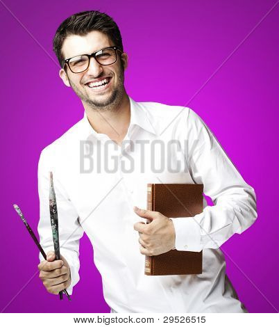 portrait of a young student holding a book against a pink background
