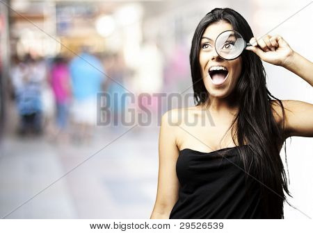 portrait of a young woman looking through a magnifying glass at a crowded place