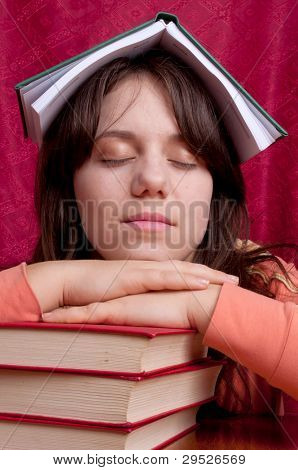 Teenage girl with a workbook on the head sleeping on a pile of books