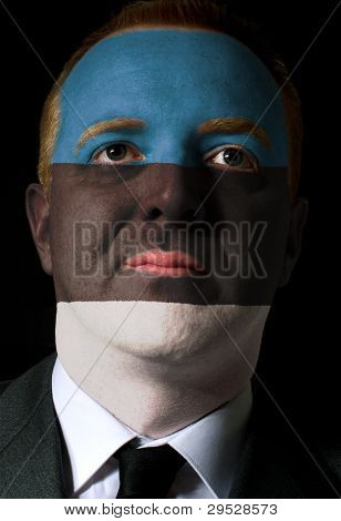 Face Of Serious Businessman Or Politician Painted In Colors Of Estonia Flag