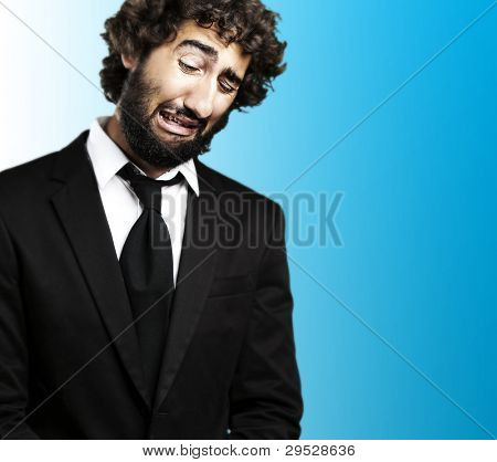 portrait of a young business man with a suit crying against a blue background