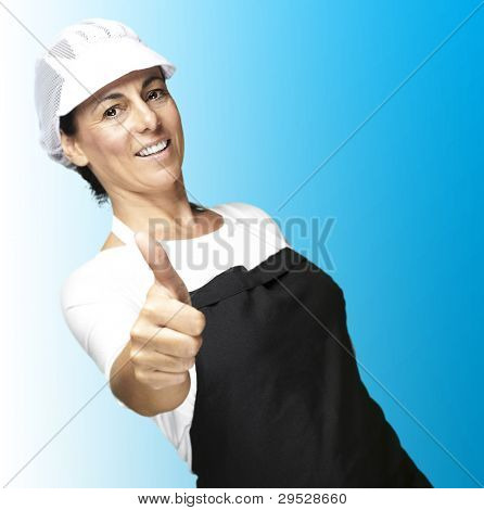 portrait of a cook wearing  an apron and mesh top hat doing okey symbol against a blue background