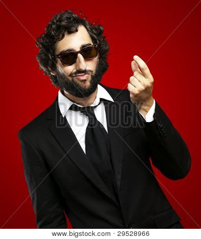 portrait of a young business man gesturing money over a red background