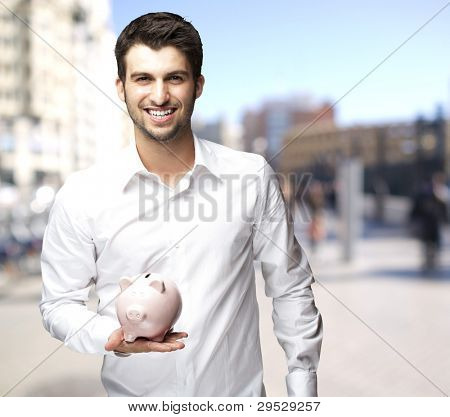 portrait of a happy young man holding a piggy bank at the street
