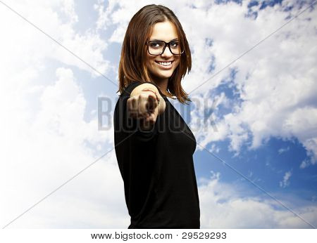 portrait of a young woman pointing against a cloudy sky