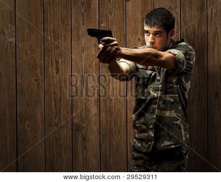 portrait of a young soldier aiming with a pistol against a wooden wall