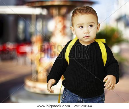 portrait of an adorable kid carrying a yellow backpack against a carousel