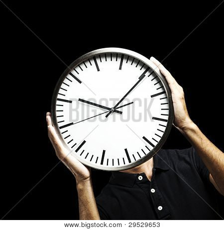 portrait of a young man hiding his face behind a clock against a black background