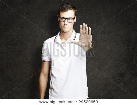 portrait of a young man doing a stop symbol against a grunge wall