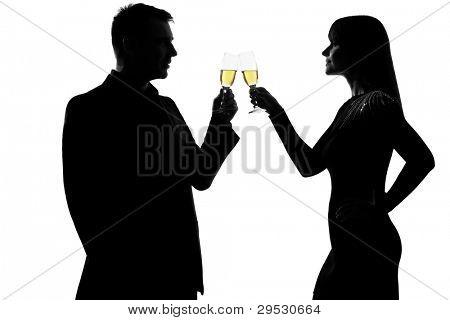 isolar um homem caucasiano e mulher bebendo champanhe torrar festejando em silhueta de estúdio