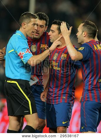 BARCELONA - JAN, 15: FC Barcelona players talk with the referee Iglesias Villanueva during the Spanish league match against R Betis at the Camp Nou stadium on January 15, 2012 in Barcelona, Spain