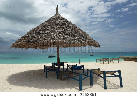 View Of Empty Deck-Chairs And Umbrella On The Beach.