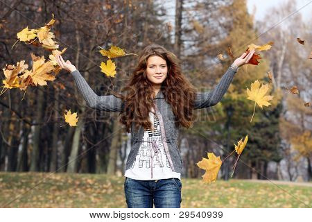 The young little girl scatters downwind maple leaves