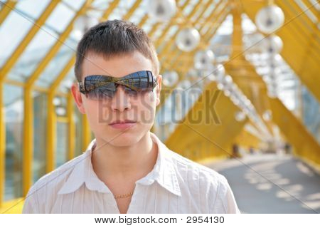 Young Man In Sunglasses On Footbridge