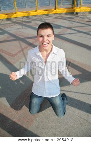 Young Man Stands On Knees On The Footbridge