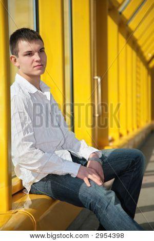 Young Man Sits On Footbridge