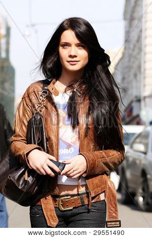 Portrait of the city girl in brown a leather to a jacket