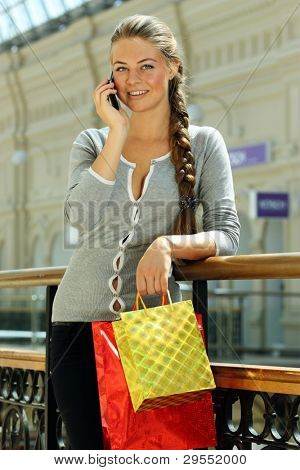 Closeup portrait of a cute young woman speaking on the mobile while holding shopping bags