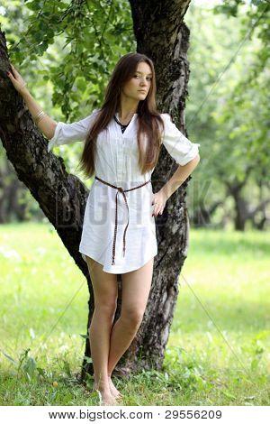 Pretty young beautiful girl standing near tree