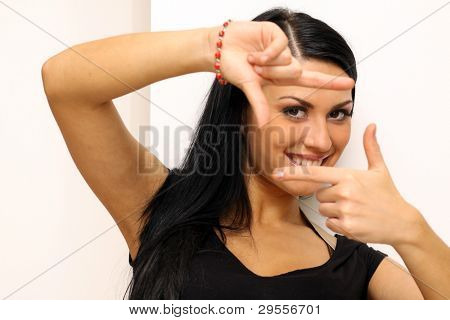 Closeup portrait of a funny woman making photografing sign standing indoors