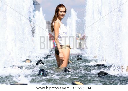 Attractive girl bathing in city fountain