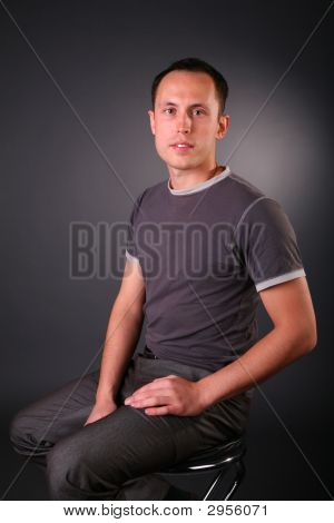 Portrait Of Young Man Sits On Stool