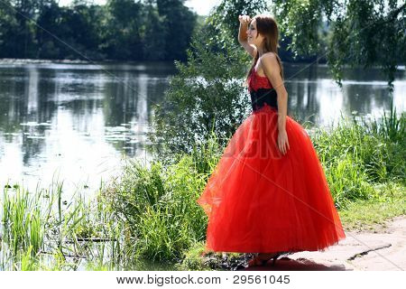 Attractive woman walking near pond in park