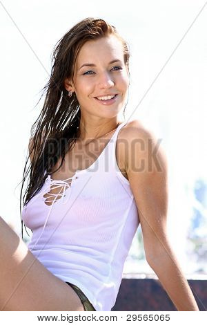 Attractive smiling girl bathing in city fountain