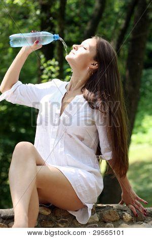 Jovem atraente bebe água mineral no Parque