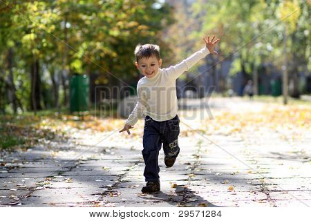 little boy runs in a summer park